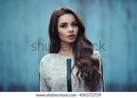 Calm or pensive girl portrait against blue old wooden wall. Pretty stylish fashionable woman in gray hoody with long curly hair looking at you. Shallow DOF, blurred background