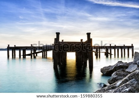 Calm scene detail of old jetty at twilight  - stock photo