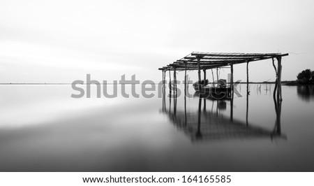 Calm scene in black and white with fisherman boat parking under the floating garage at Jubakar Beach Tumpat Kelantan. black and white (fine art)  - stock photo
