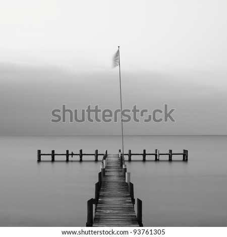Calm scene in black and white with wooden jetty on a cold day - stock photo