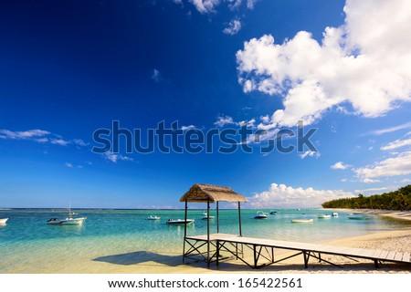 Calm scene with jetty, boats  and turquoise water in Mauritius - stock photo