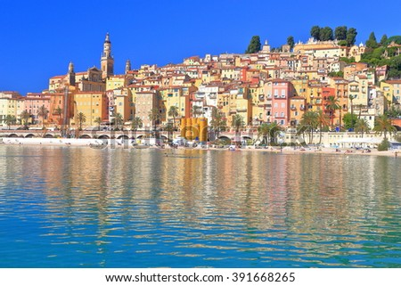 Calm sea and distant town of Menton in sunny day, French Riviera, France