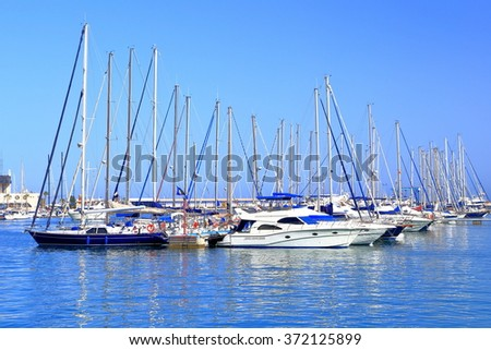 Calm sea and sail boats by the pier inside the harbor of Alicante, Spain - stock photo