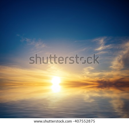 Calm sea, golden clouds on the blue sky and the last rays of the sun. Natural seascape