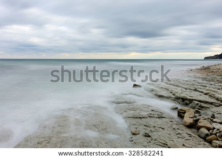 Calm sea long exposure shot.Stones in mysterious mist of sea waves - stock photo