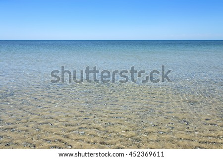 Calm sea surface near coastline. Seascape in sunny day under clear skies.