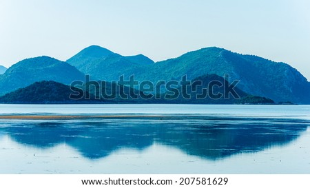 Calm sea with distant mountains and reflection in water - stock photo