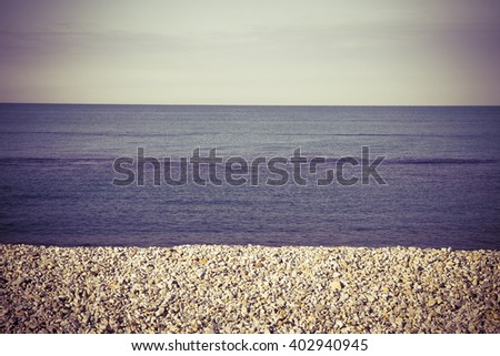 Calm sea with white stones on the beach - toned image - stock photo