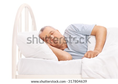 Calm senior man sleeping in a bed covered with a white blanket isolated on white background - stock photo