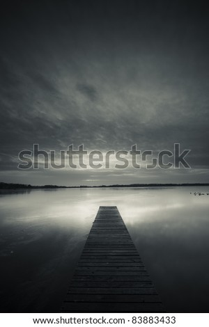 Calm sunset with a jetty on a lake - stock photo
