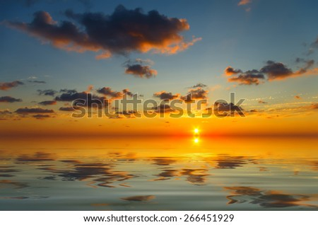Calm sunset with occasional clouds in the bright blue sky - stock photo