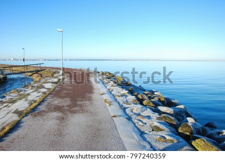 Calm water by a frosty harbor pier at Farjestaden on the swedish island Oland in the Baltic Sea