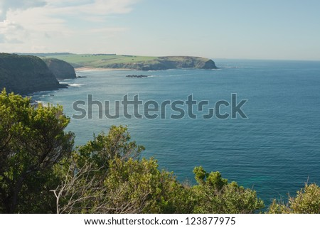 Calm water in bay at Cape Schanck with rock, bush and green meadows and clouds in background in Victoria, Australia