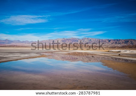 Calm water of a pond mirroring the mountains of Death Valley National Park in California. - stock photo