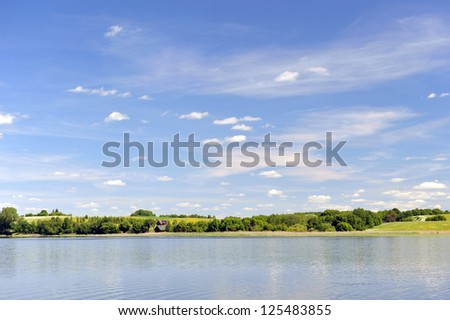 calm water of  lake, woods on other side and  blue sky. landscape - stock photo