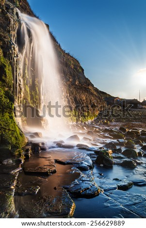 Calm waters at slack tide with a torrential waterfall splashing on the rocks - stock photo