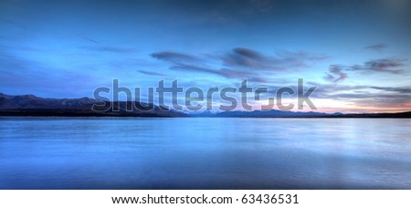 calm waters of a glacier lake with mountains behind