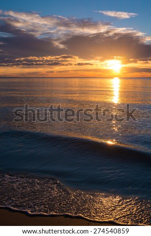 Calm waters of a Mediterranean beach at sunrise - stock photo
