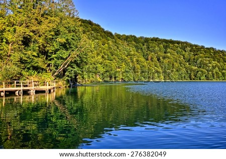 Calm waters with reflections amongst lush greenery, Plitvice Lakes National Park, Croatia - stock photo