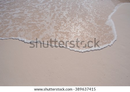 Calm wave on a sandy shore - stock photo