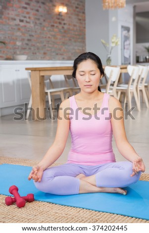 Calm woman doing yoga on mat in living room
