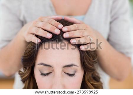 Calm woman receiving reiki treatment on white background - stock photo