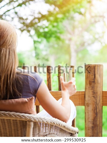 Calm woman relaxing outdoors, back side of female sitting on the chair on terrace, drinking water and enjoying beautiful nature view - stock photo