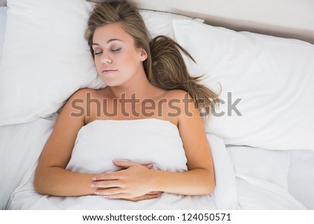 Calm woman sleeping in white bedroom during the day - stock photo