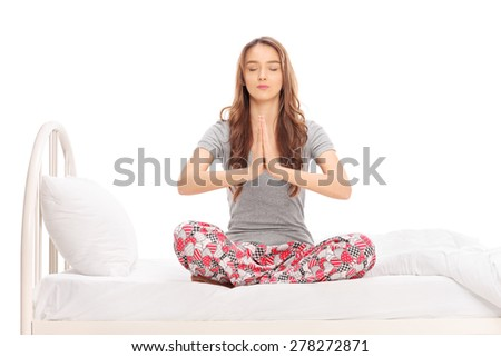Calm young woman in pajamas meditating seated on a bed isolated on white background - stock photo