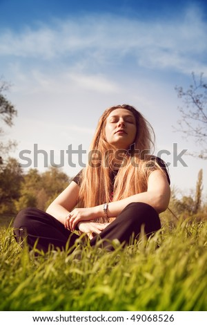 Calm young woman relaxing in sunny grass field