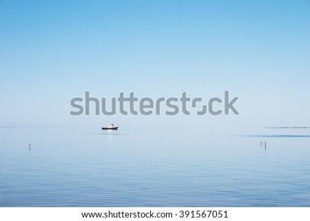 Calmness Small boat in the morning calm sea - stock photo