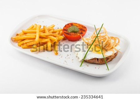 calorie breakfast :scrambled eggs with fries, fried tomatoes and  cutlets  - stock photo