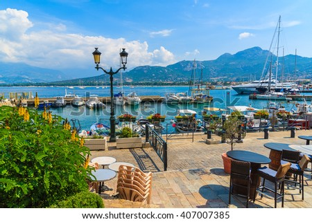 CALVI, CORSICA ISLAND - JUN 29, 2015: chairs and tables of a restaurant in Calvi port. This town has luxurious marina and is a very popular tourist destination.