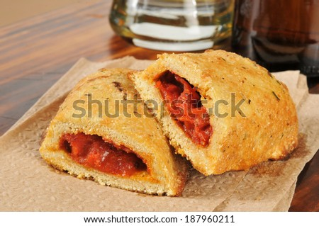 Calzones or pizza pockets and a mug of beer - stock photo