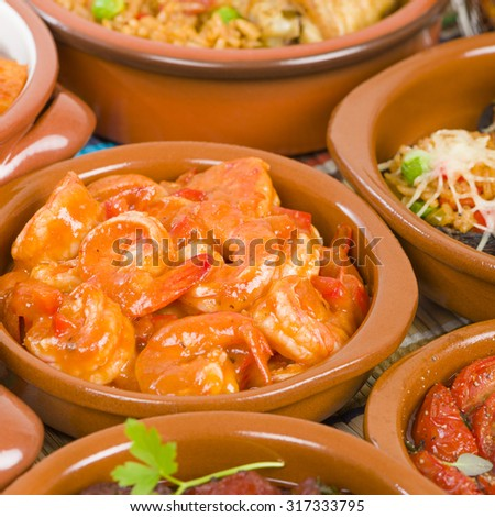 Camarones Enchilados - Cuban style shrimp in a tomato based sauce. Surrounded by other tapas dishes.