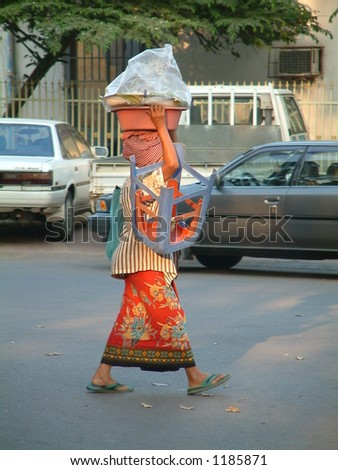 Cambodian woman carrying load accross the road - stock photo