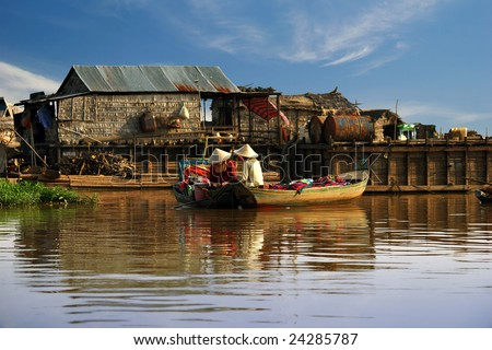 Cambodian women sail on a boat near the fishing village of Tonle Sap Lake - stock photo