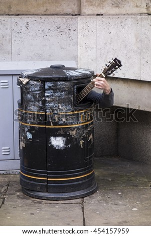 CAMBRIDGE, ENGLAND - MAY 9, 2015: A street musician plays guitar from the unusual location of the inside of a trash bin near Cambridge University in England. - stock photo