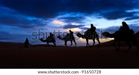 Camel train silhouetted against colorful sky crossing the Sahara Desert, Morocco - stock photo