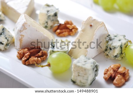 Camembert and  blue cheese on plate with grape and walnut closeup - stock photo