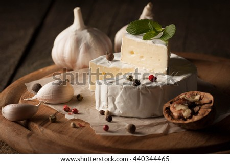 Camembert and brie cheese on wooden background with nuts spices and garlic. Italian food. Dairy products. - stock photo