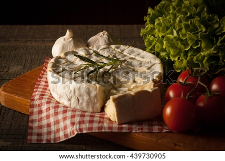 Camembert and brie cheese on wooden background with tomatoes, lettuce, spices and garlic. Italian food. Dairy products. - stock photo