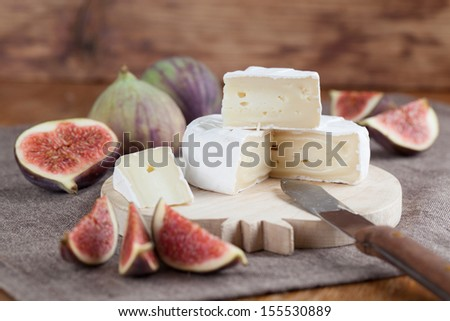 Camembert and fresh figs on a cutting board - stock photo