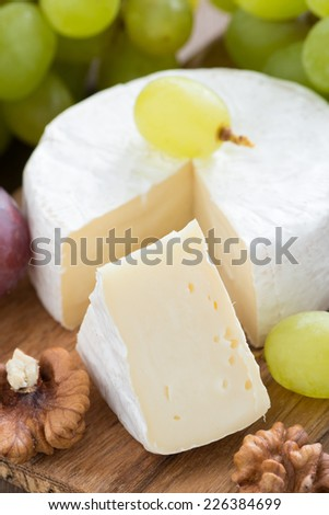 camembert and fresh green grapes, vertical, close-up