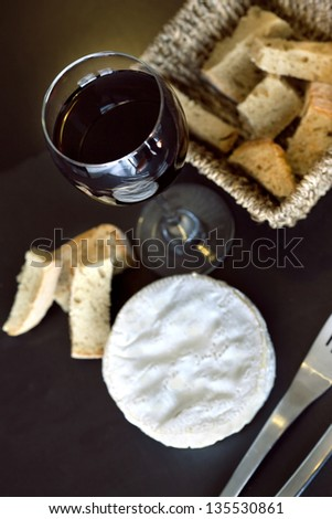 Camembert, bread and glass of red wine on a table - stock photo