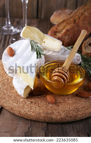 Camembert cheese, nuts, honey and bread on cutting board on wooden background - stock photo