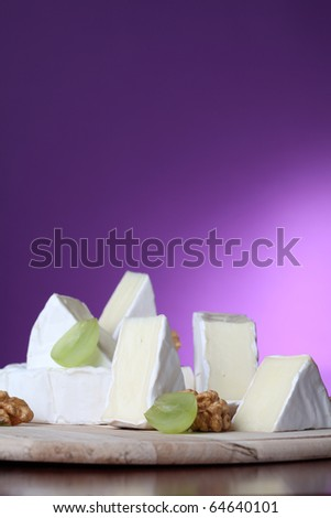 Camembert cheese on cutting board with walnuts and grapes - stock photo
