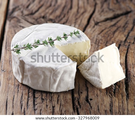 Camembert cheese on old wooden table. - stock photo