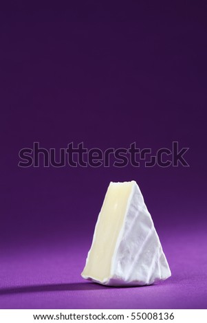 Camembert cheese on purple background. Copy space. - stock photo