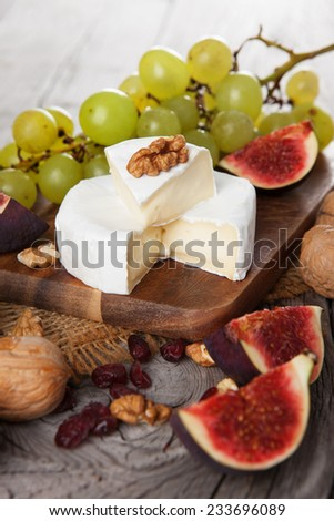 Camembert cheese with figs, nuts and cranberry on dark wooden background